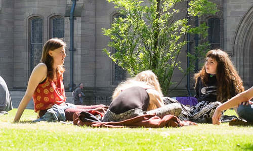 Students on grass across from Whitworth Hall